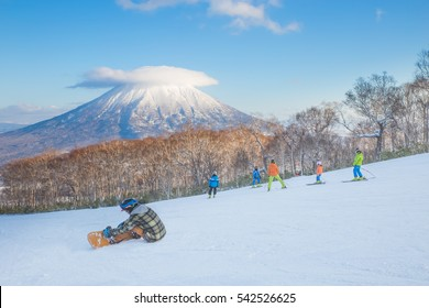 People skiing on the snow slope and Mt.Yotei as a background in Niseko Ski area, Hokkaido, Japan