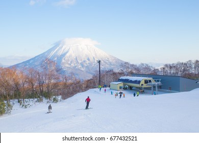 People skiing on the white snow slope with Mt.Yotei as a background in Niseko Ski area, Hokkaido,Japan. Winter landscape, winter activity and recreation.