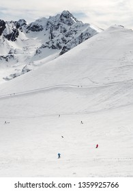 People skiing and peaks of the mountains in the background