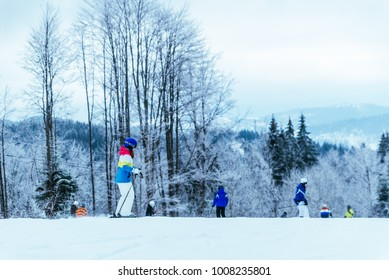people skiing and snowboarding at winter carpathian mountains