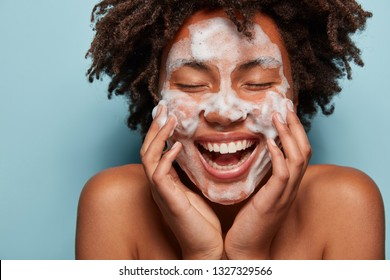 People, skin care and rejuvenation concept. Pleased dark skinned woman with soft skin, applies white foam on face, touches cheeks, smiles broadly, cares of hygiene, feels relaxed and satisfied