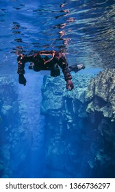 People Snorkeling swimming diving in  blue glacier water in famous fissure Silfra between two tectonic plates in the national park Thingvellir in Iceland. Blue transparent water deep colors Pingvellir