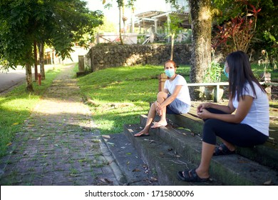 People social distancing while wearing mask.Neighbours with facemask gossiping in the outdoor.Corona Virus pandemic.