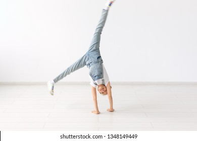 people, sport and children concept - pretty little girl doing gymnastics over white background