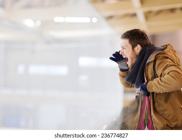 people, sport, emotions and leisure concept - young man supporting hockey game and shouting on skating rink