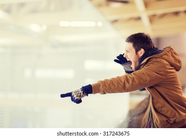 people, sport, emotions and leisure concept - young man supporting hockey game, pointing finger and shouting on skating rink