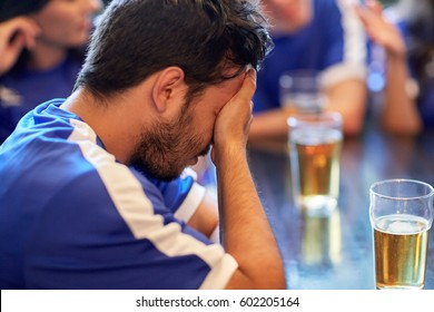people, sport and fail concept - close up of sad football fan at bar or pub