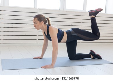 People, sport and fitness concept - slim young woman in sportswear doing donkey kick exercise