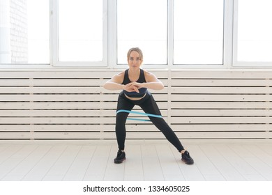 People, sport and fitness concept - young woman training with workout band in gym