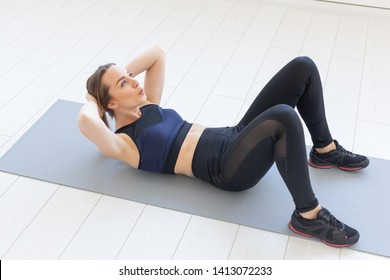 people, sport and fitness concept - young fitness woman doing abs crunch exercise on floor at home