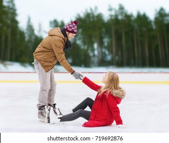 people, sport and leisure concept - smiling man helping women to rise up on skating rink over winter outdoor background