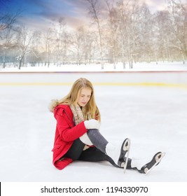 people, sport, trauma, pain and leisure concept - young woman fell down on outdoor skating rink and holding to her knee