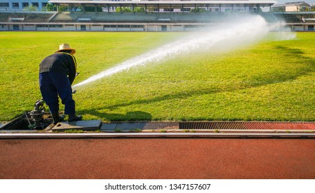 People are spraying grass in football field.