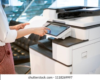 people stand by a copy machine  and hold on a paper for paper copy