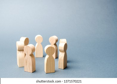 People stand in a circle on a gray background. Wooden figures of people. discussion, cooperation. Communication. Business team, teamwork, team spirit. Selective focus