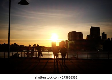 People stand in an early evening Vancouver sunset