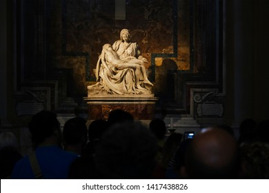 People stand in front of the Pieta which is a work of Renaissance sculpture by Michelangelo Buonarroti, housed in St. Peter's Basilica, Vatican City on April 27, 2019.