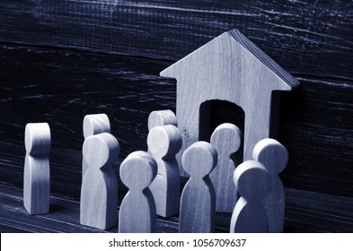 People are standing at the entrance to the building and create a hurdle to enter. Enraged crowd of people waiting. The concept of a rally meeting and strike. Wooden figurines house on dark background