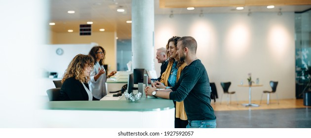 People standing in the hall of a municipal office and talking with the administrators. Municipality office reception with people being assisted by the receptionist. - Shutterstock ID 1927592057