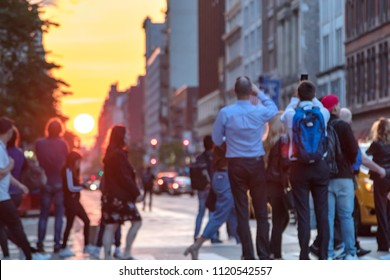 People standing in the middle of 23rd street and Broadway photographing the sunset in Manhattan, New York City