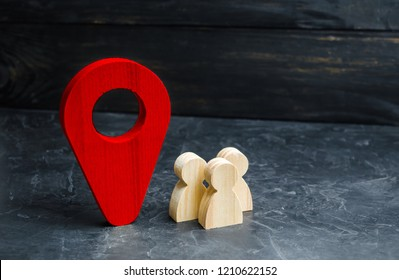 People are standing near the location marker. Concept of navigation and venue. Tourism and travel. Spying on the citizens.. Orientation around the city, the location of events and events.