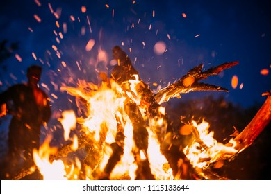 People standing next to Beach bonfire with sparks flying around