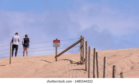 "People standing on an edge of a cliff of Cape Kiwanda behind protective barrier. A sign posted on a barrier read ""Danger"" and ""Do not go beyond this point""."