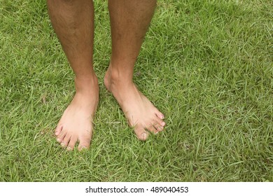 People standing on the grass without shoes.