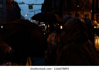 people are standing on the street in rainy weather with umbrellas
