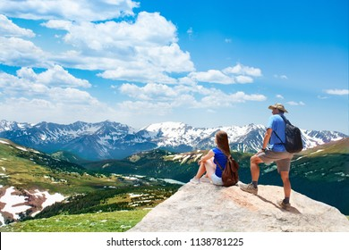People standing on top of the mountain looking at beautiful view. Early summer landscape with green meadows and snow covered mountains.  Trail Ridge Road. Rocky Mountains National Park, Colorado, USA.