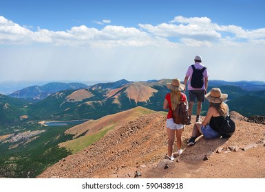People standing on top of mountain rock. Family looking at beautiful summer mountains landscape,from Pikes Peak summit on hiking trip.  Pike National Forest, Cascade, Colorado, USA