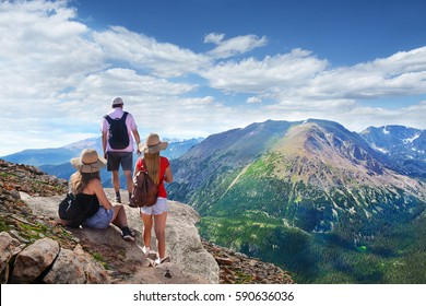 People standing on top of mountain rock. Family looking at beautiful summer landscape from Trail Ridge Road. Rocky Mountain National Park landscape. Colorado, USA.