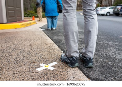 People standing waiting in line far apart to maintain social distance distancing during covid-19 coronavirus outbreak with mark cross signs on sidewalk pavement by grocery food store shop shopping