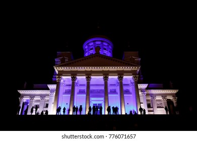 People stant in front of illuminated Helsinki St Nicholas cathedral at night