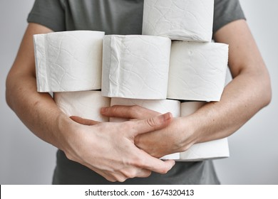 People are stocking up toilet paper for home quarantine from coronavirus. Woman holds many rolls of toilet paper