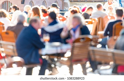 People at a street cafe in Europe defocused image as background