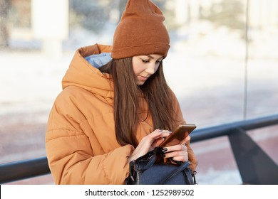 People, street style and technologies concept. Young woman wears brown hat, jacket, poses at bus station, surfes internet on mobile phone, chats with firend while waits for transport. Urban life.