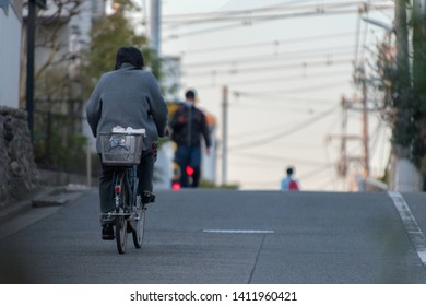 People in the streets of Tokyo, one person riding a cycle alone after the sunset.