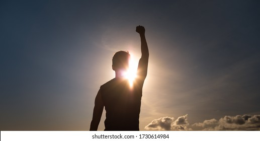 People, strength, power, and never giving up concept. Strong man with fist up to the sky.