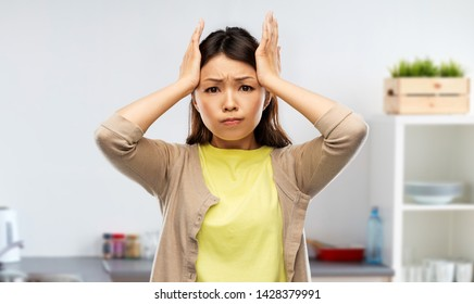 people, stress and cooking concept - stressed asian woman holding to her head over kitchen background