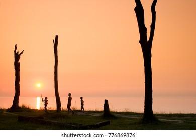 People stroll on the Coastline in Sunset