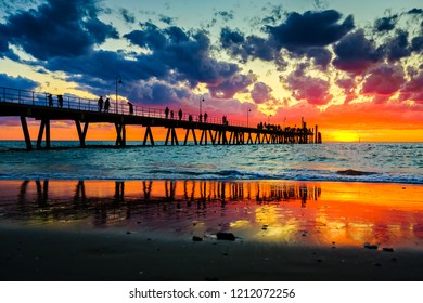 People stroll on Glenelg jetty at sunset sky splashed with colourful hues of red, orange and blue in Adelaide, South Australia