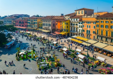 People are strolling among flower stands during Saturday market on the piazza bra in the Italian city Verona