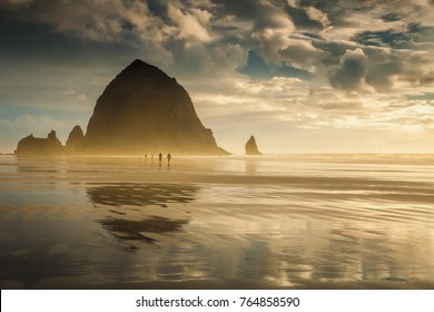 People strolling at sunset allong Oregon's Cannon Beach