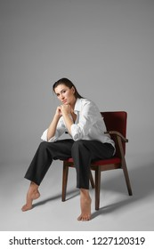 People, style, fashion, clothes and interior concept. Vertical portrait of stylish beautiful barefoot young female in men's formal clothing, sitting in chair like man with her legs wide apart