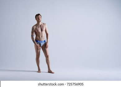 People, style and fashion concept. Full length isolated portrait of handsome muscular athletic adult European male model with beard posing in studio for underwear advertisement or commercial.