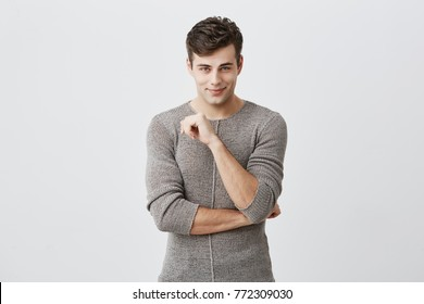 People, style, fashion concept. Handsome young European male with stylish haircut and blue eyes, wearing sweater posing indoors, keeping arms folded, looking at camera with handsome flirting smile