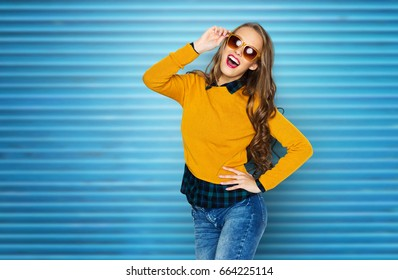 people, style and fashion concept - happy young woman or teen girl in casual clothes and sunglasses having fun over blue ribbed wall background