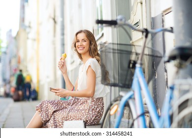 people, style, technology, leisure and lifestyle - happy young hipster woman with smartphone and fixed gear bike eating ice cream on city street