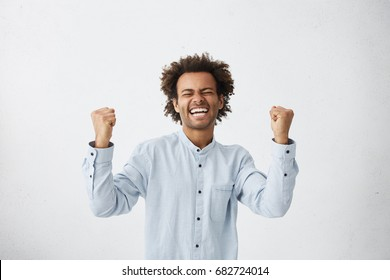 People, success, triumph, victory, winning and celebration. Happy successful young black businessman screaming Yes and raising clenched fists in the air, feeling excited after he made good deal
